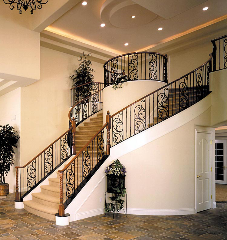 Lifetime Luxury Amazing Stair Design - staircase that forks into two separate staircases that go round a cylindrical volume to join again at the split level with wooden handrails and dark iron balustrade with decorations -146