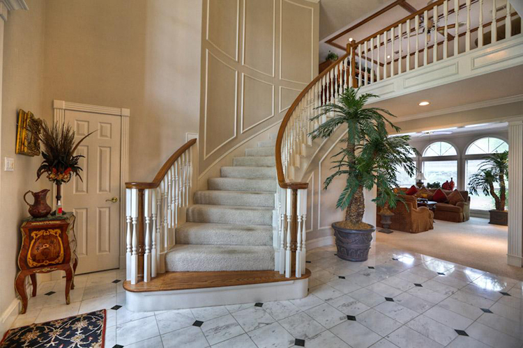 Lifetime Luxury Amazing Stair Design - curved staircase turning right with stairs covered with a white carpet, white wooden balusters, wallnut handrails, white skirt board with decorations -323