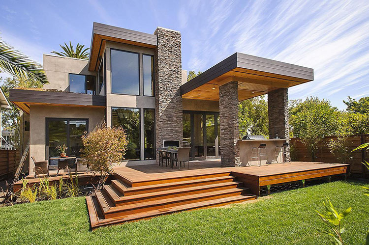 Lifetime Luxury - split level wooden patio with staircase and tow storey cottage with grey stone columns and chimney - Unique Architecture Design043