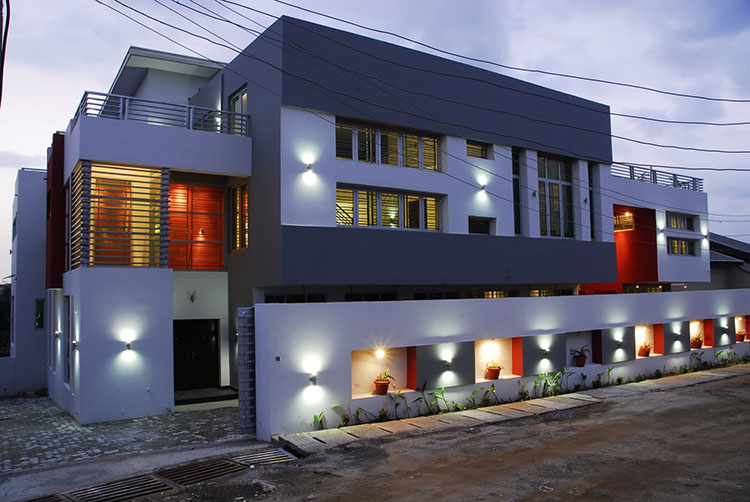 Lifetime Luxury -three storey massive building in white and dark grey with small balconies on its sides - Unique Architecture Design140