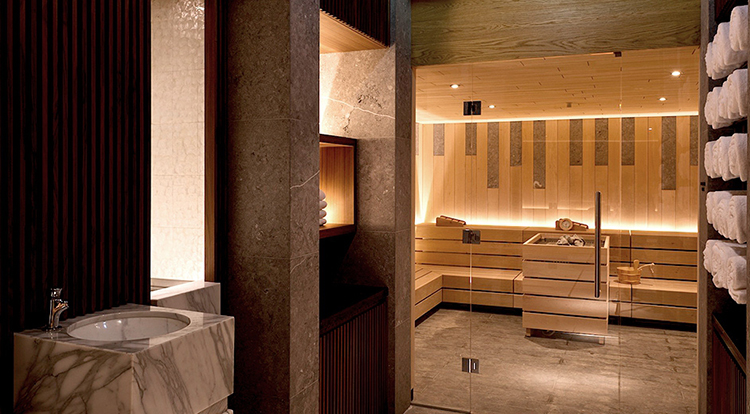 Luxury Home Sauna - view from outside of an in-home sauna with wall covered with wooden panels, wooden benches, huge glass panel entry door - LifetimeLuxury031