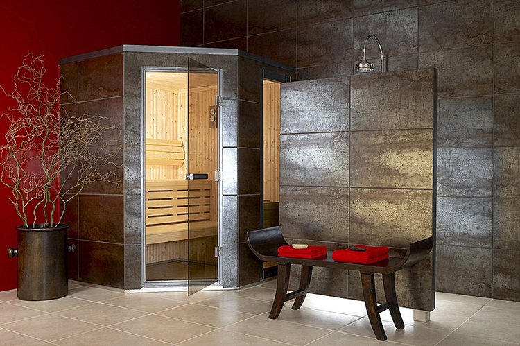 Luxury Home Sauna - Indonesian style stools in foreground and metallized dark wall panel, in background glass door open leading inside the sauna - LifetimeLuxury091
