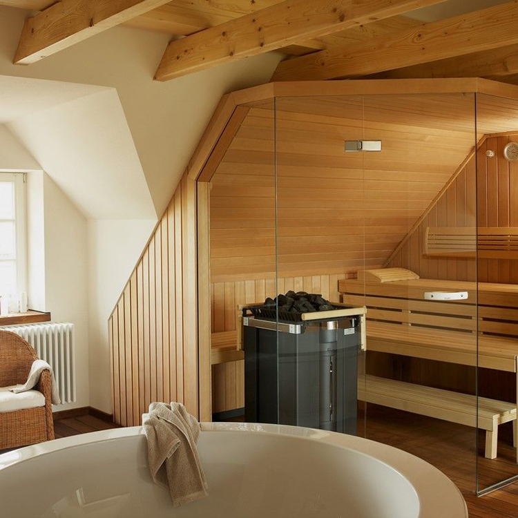 Luxury Home Sauna - an attic with an in-home sauna on the right. Detail of the circular bathtub on the foreground, and immediately after the glass panel front wall of the sauna cabinet with the dark metal brazier - LifetimeLuxury177