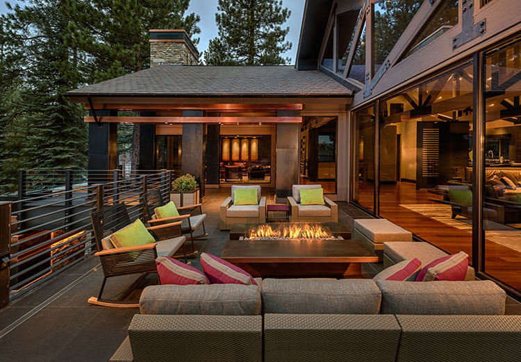 Luxury Patio Ideas - wide balcony with couch and armchairs set around a central fireplace on the foreground and outdoor patio laying on the balcony itself on the background - LifetimeLuxury008