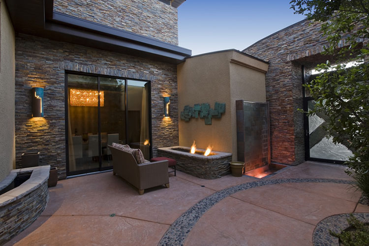 Luxury Patio Ideas - outdoor patio iin villa with stone walls and pod-shaped fireplace in a corner on the right with couch in the front - LifetimeLuxury027