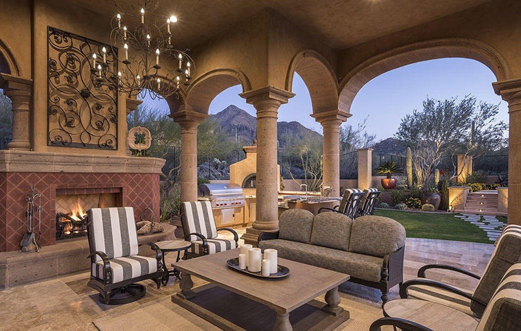Luxury Patio Ideas -covered patio with columns and round arches open on a huge lawn with desert mountains in the background - LifetimeLuxury031