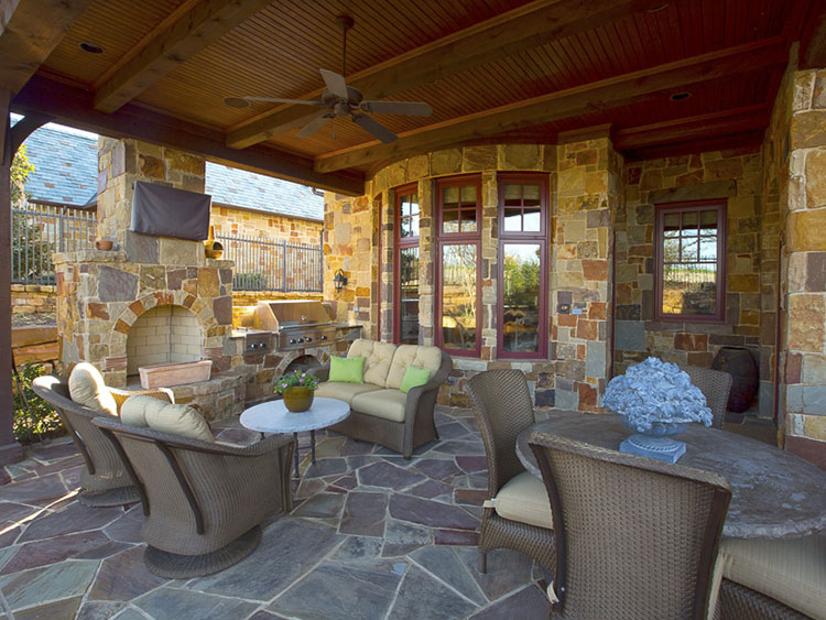 Luxury Patio Ideas - covered patio with wooden floor paved with stone. Stone mantelpiece with cooking area on the right and living area furnished with armchairs, couches and round tables in front - LifetimeLuxury059