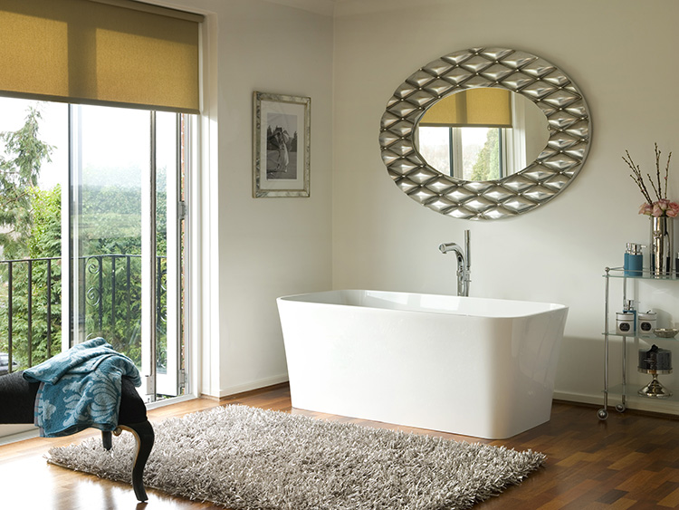 05. Luxury bath gallery - Edge Bath - white bathtub in a white room with parquet on the floor, square fucsia carpet, round vanity mirror with thick silver frame.