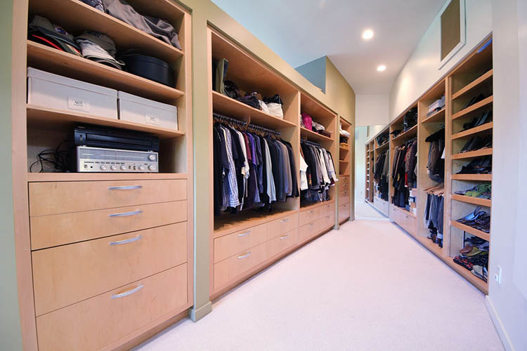 Lifetime Luxury - Luxury Closet Ideas074 - funnel shape room with modern closets on the wall. On the right, a huge shoe racks and then three clothe racks; on the left, drawers and shelves, and then two clothe racks -