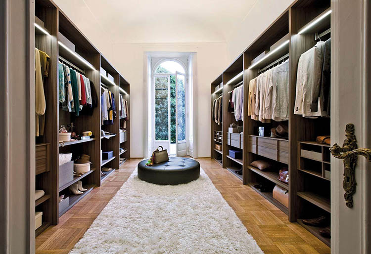 Lifetime Luxury - Luxury Closet Ideas078 - closets on the right and the left walls, long and narrow french window in the foreground and in the middle of the wall, round leather bench in the middle of the room -