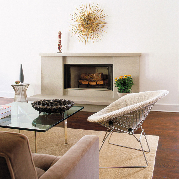 18. Luxury chairs gallery - Harry Bertoia Duamond Chair with white pillow in a living room with a glass table in front and a fireplace in the background