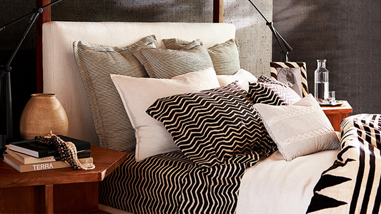 0.8 decorative pillows gallery - Ralph Lauren Home-bed with several pillows set on four rows - first row: 3 grey pillows; second row, 2 white pillows, third row two balck and white stripe pillow, fourth row one light grey pillow with decorations