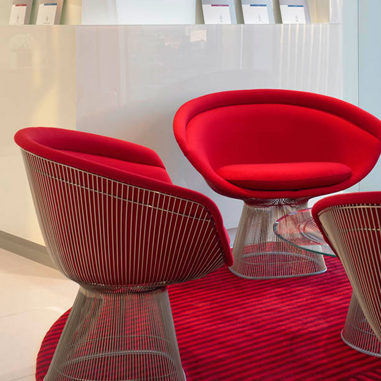 11. luxury cahirs gallery - three Warren Platner's Lounge Chairs with red pillows on a red tarpet